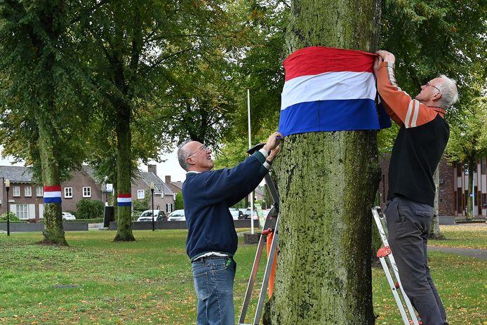 Toon Hendriks is met behulp van zijn broer Martien bezig met het versieren van de bomen op het 14 Oktoberplein in Overloon.