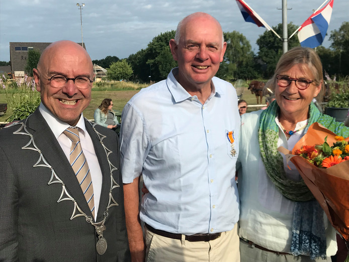 Jan van de Graaf wordt geflankeerd door zijn vrouw Josien en burgemeester Kees van Rooij.