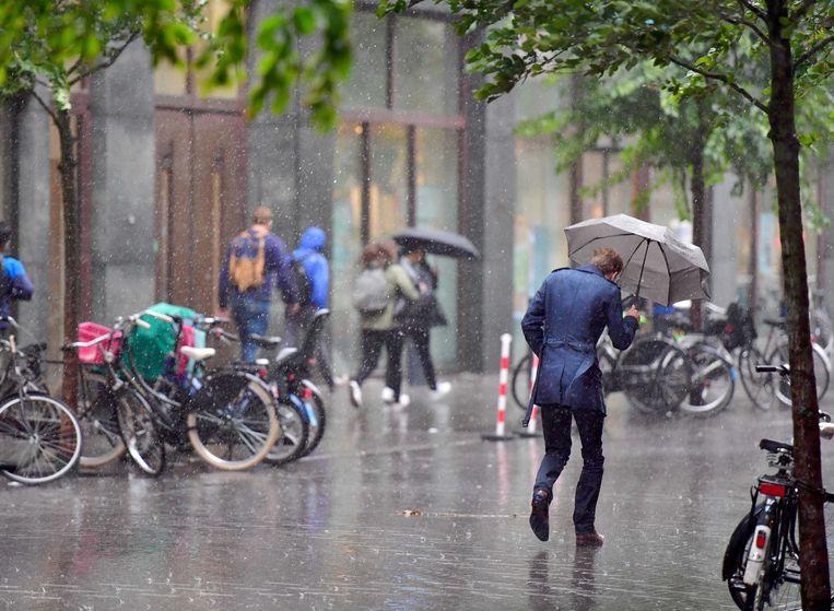 Een voorbijganger loopt door een stevige regenbui op de Turfmarkt in Utrecht. Beeld ANP