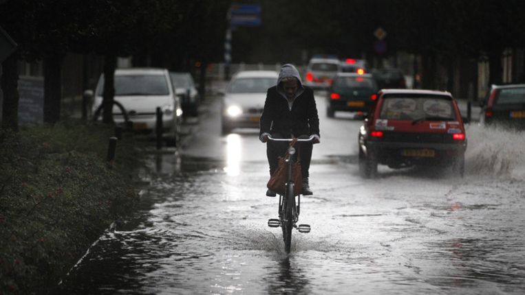 Een fietser probeerde afgelopen zomer droge voeten te houden. Beeld ANP