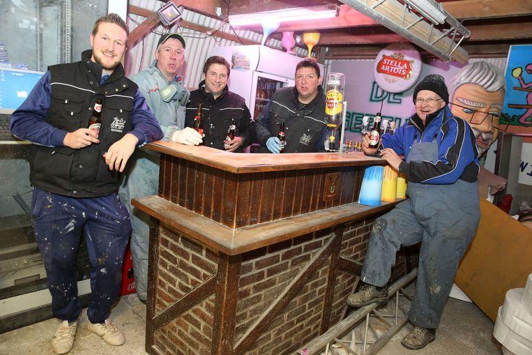 De leden ontspannen tijdens het werk in de hangar even met een fris pintje aan de toog van het gesloten carnavalscafé.