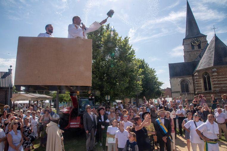 Deken Yvan Stassijns doopt de reuzen van Massemen vanop een hoogtewerker.