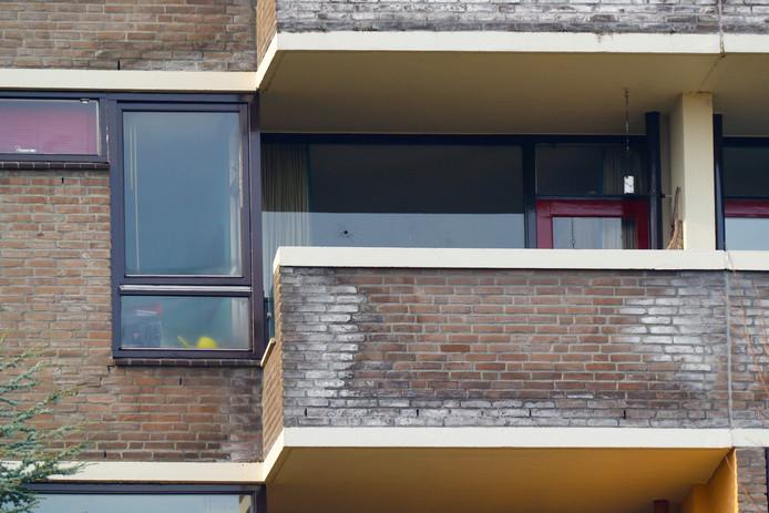 Een kogelgat in de ruit van een appartement