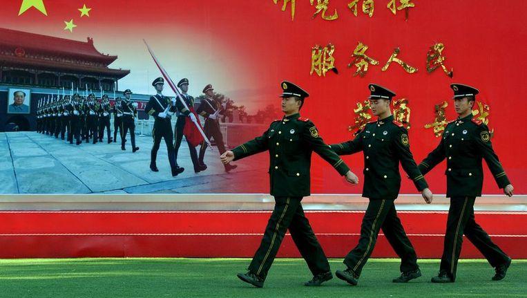 Chinese politieagenten marcheren voor een poster van marcherende agenten Beeld afp