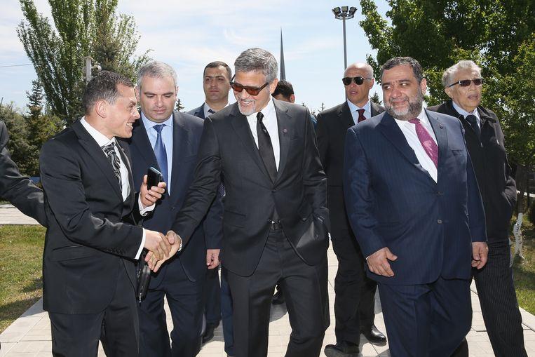 Acteur George Clooney (midden) en vriend Ruben Vardanyan (paarse das), de Russisch Armeense zakenmandie ooit de Troika bank oprichtte, bij de herdenking van de Armeense genocide in 2016 in Jerevan. Beeld Getty Images Europe