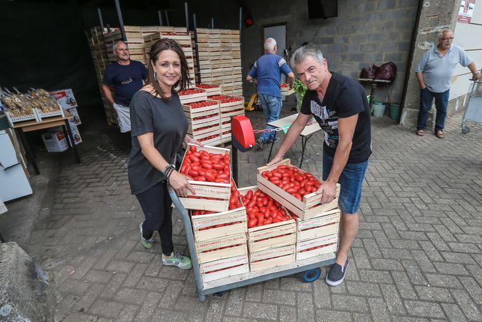 Verkoopster Manuela Rotilio helpt Mario La Monaca om zijn kisten met in totaal 110 kilogram tomaten in te laden.