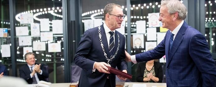 De nieuwe burgemeester van Boxtel Ronald Meygaarden (links) krijgt een gloednieuwe cassette om de ambtsketen in op te bergen van zijn voorganger Fons Naterop.
