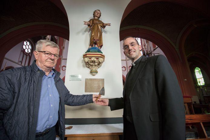Bernard Fleerakkers (l) van Heemkunde Werkgroep Reusel biedt kapelaan Sacha Steijaerts (r) de troffel aan.