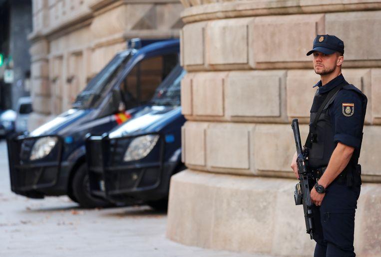 Een agent van de Spaanse nationale politie staat voor het Hooggerechtshof in Barcelona. Beeld REUTERS