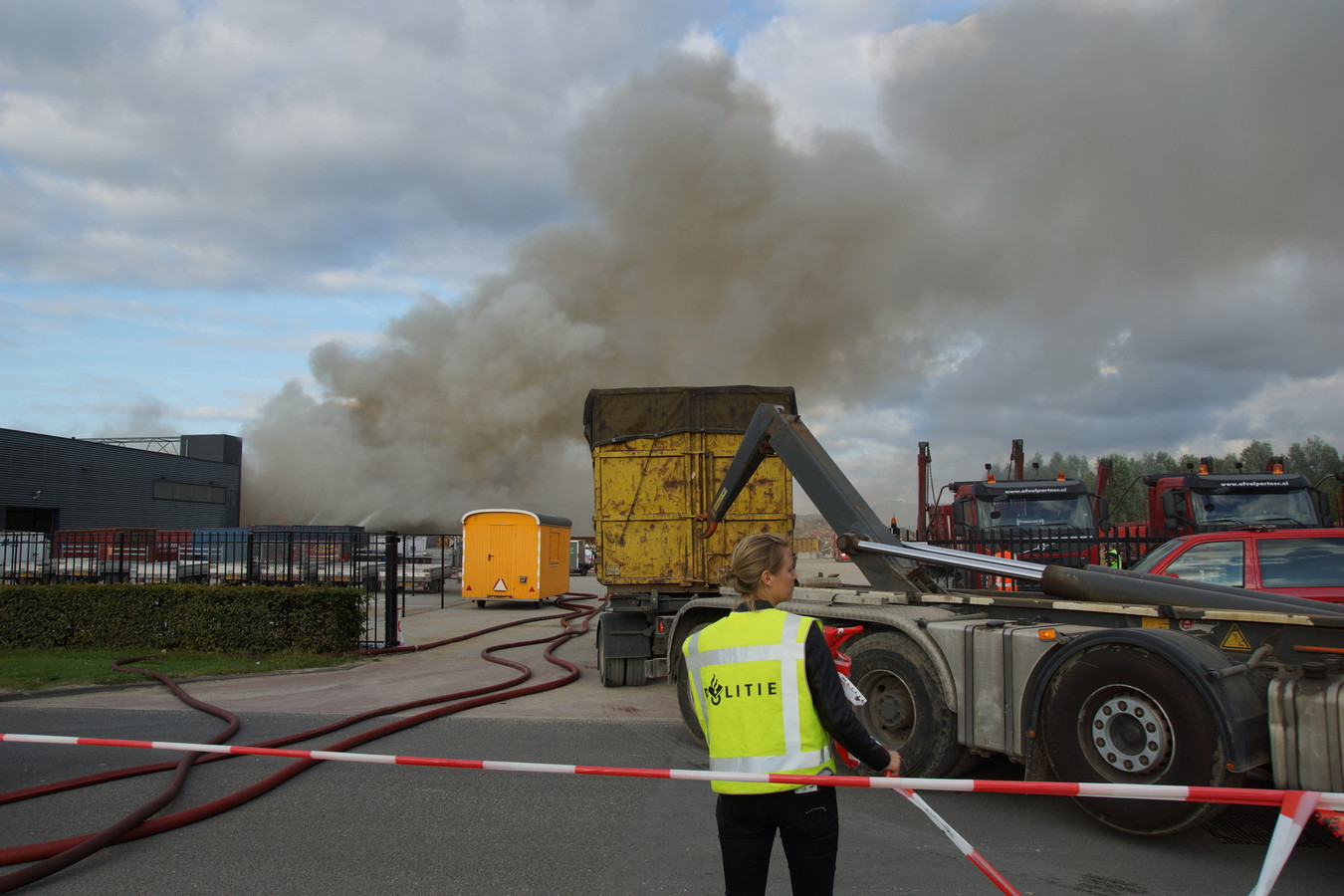 Containers met afval worden van het terrein gereden.