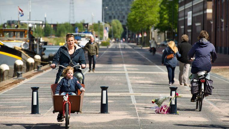 Een vrouw fietst over de Veemkade. Op de paaltjes werden na het ongeluk reflectoren geplaatst Beeld Klaas Fopma, www.klaasfopma.nl