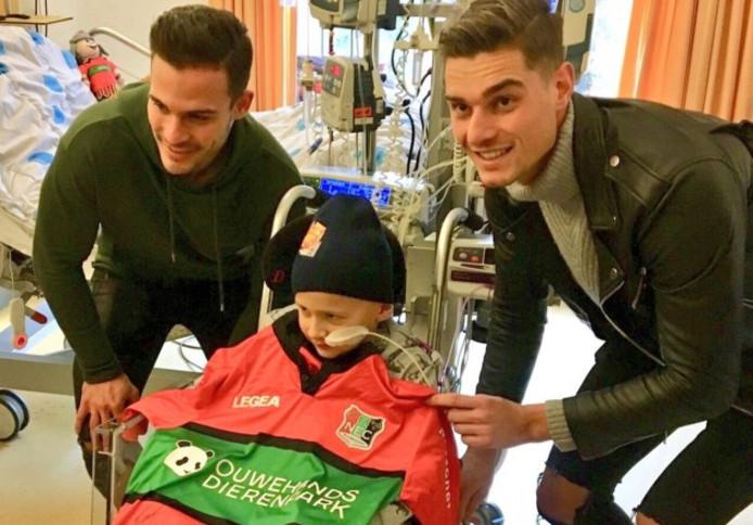 NEC-voetballers Guus Joppen (links) en Joshua Smits gaan op de foto met Luca.