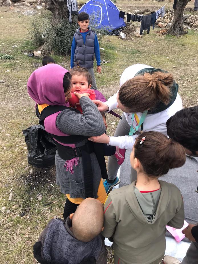 Vrijwillliger van Because we Carry helpt een vluchtelinge met haar kind (2)