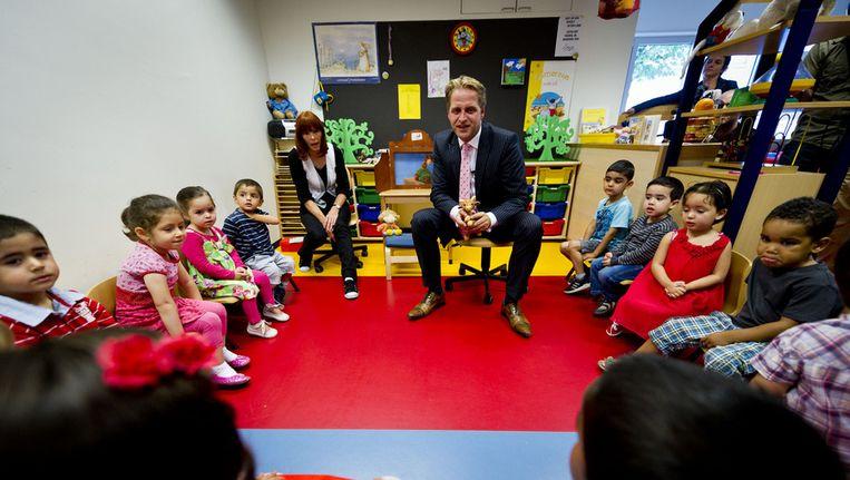 Wethouder Hugo de Jonge, twee jaar geleden in de kring bij twee- en driejarigen kinderen die op de Dr. J. Woltjerschool in Rotterdam beginnen aan hun schooljaar in de nulgroep. Beeld anp