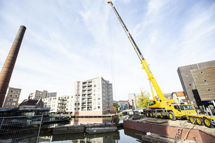 Met een kraan worden de damwandplaten uit het water getrokken en heeft de binnenstad van Almelo weer een haven.