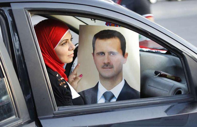 Een Syrische vrouw toont een poster van Assad om haar support voor hem te uiten. Beeld afp