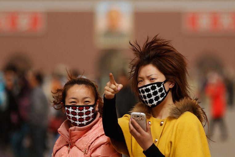 Mensen proberen zich met mondkapjes te beschermen tegen de luchtvervuiling in Peking. Beeld null