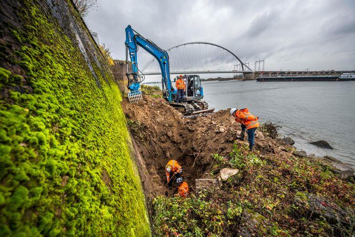 Medewerkers van Waterschap Rivierenland leggen een deel van de fundering van de tweehonderd jaar oude kademuur bloot voor inspectie.