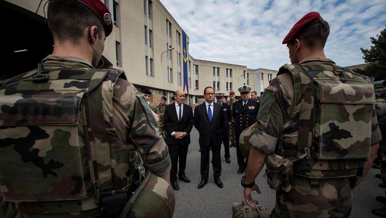 De Franse president Hollande (midden) en minister van Defensie Le Drian, maandag op een legerbasis met militairen belast met terreurbestrijding. Beeld Reuters