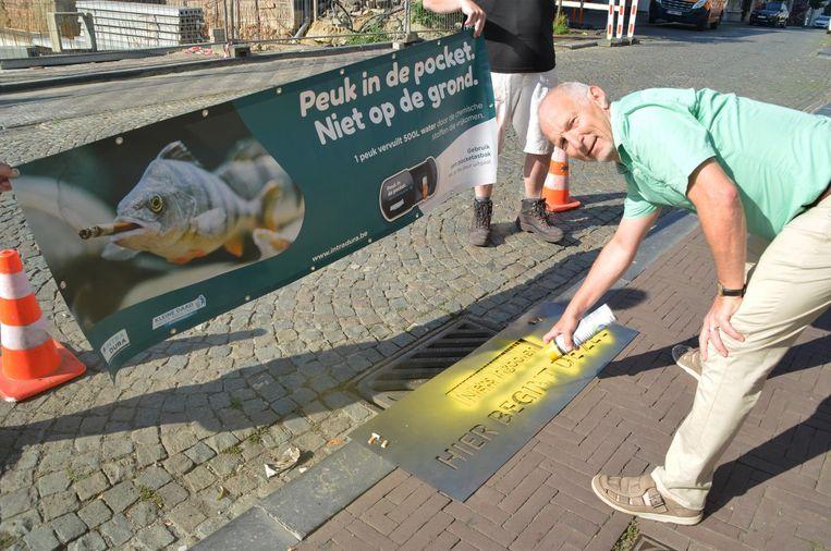 Milieuschepen Eddie Boelens schildert de boodschap 'hier begint de zee' bij een putdeksel.