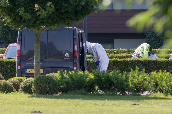 Forensisch medewerkers doen onderzoek bij een bestelbusje op een parkeerplaats waar een persoon is doodgeschoten.