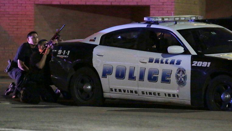De politie schuilt achter een politie-auto in Dallas. Beeld ap