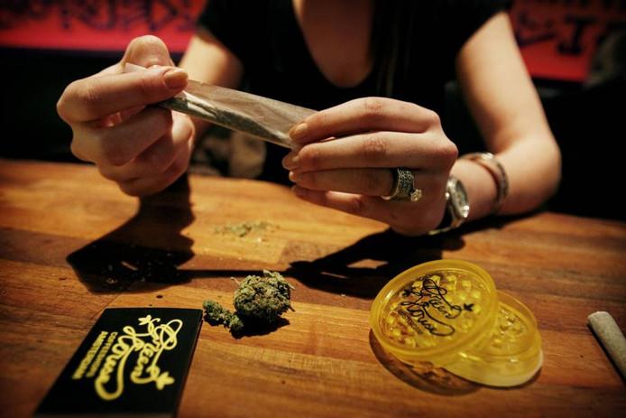 Bezoeker van een coffeeshop draait een verse joint.