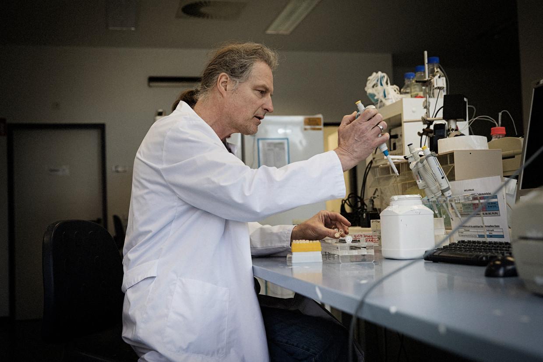 Olfert Landt in zijn laboratorium van zijn Berlijnse biotechbedrijfje. De foto is genomen door het raam op een ladder, want vanwege besmettingsgevaar mogen alleen vaste medewerkers nog naar binnen. Beeld Daniel Rosenthal / de Volkskrant