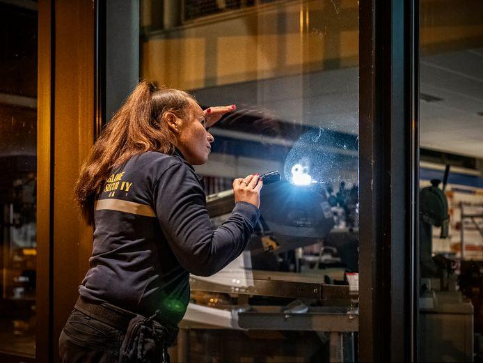 Miranda Vlaswinkel checkt door de ramen van een Achterhoeks bedrijf of er geen ongewenste personen binnen zijn.