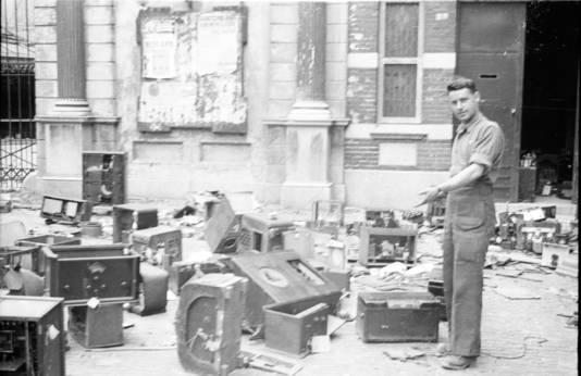 Een foto van kort na de oorlog toont de Joodse Godsdienstschool aan de Kippenmarkt, met door de Duitsers gevorderde radio's op straat. Een geallieerde militair wijst naar de plek