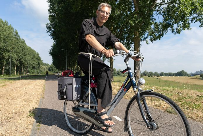 Pastoor Roland Putman op zijn fiets in zijn bruine habijt.