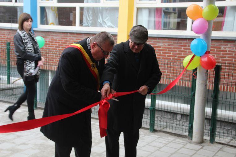 Burgemeester Uyttendaele en schepen De Mulder knipten het lintje aan de vernieuwde speelplaats plechtig door.