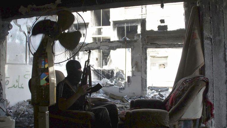 Een lid van het Vrije Syrische leger zit in een kapotgeschoten huis Beeld reuters