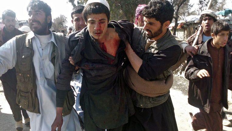 Een gewonde jongen wordt weggedragen van een protest tegen de koranverbranding. Beeld afp