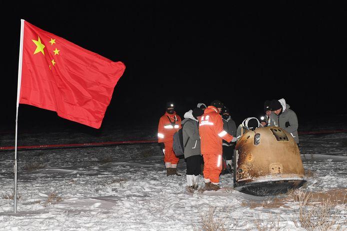 Les chercheurs travaillent autour de la capsule de retour lunaire Chang'e-5 transportant des échantillons de lune à côté d'un drapeau national chinois, après son atterrissage dans la région autonome de Mongolie intérieure du nord de la Chine, le 17 décembre 2020.