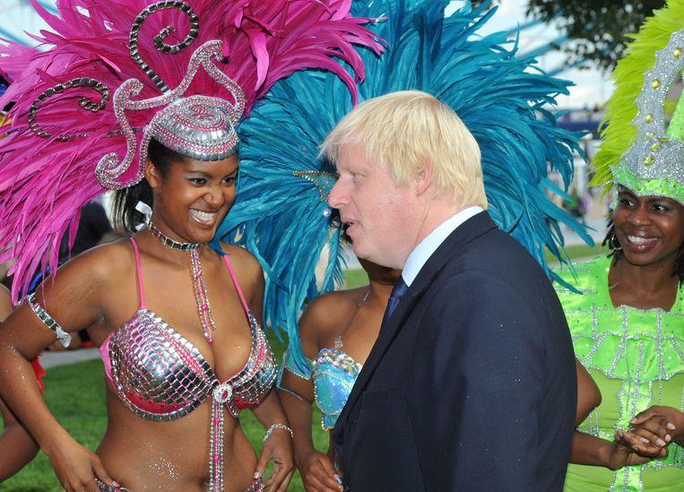 Burgemeester Boris Johnson pratend met een lid van de Genesis Mas Band (2011). Beeld EPA