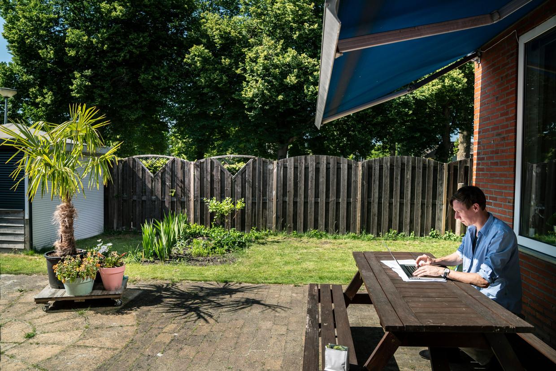 Om de warmte te ontvluchten, werkt deze docent van de Hanzehogeschool Groningen in de tuin. Normaal werkt hij op zolder. Beeld Reyer Boxem