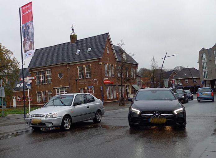 Auto's moeten om de geparkeerde wagen op de rijbaan van de Dorpsstraat heen rijden.