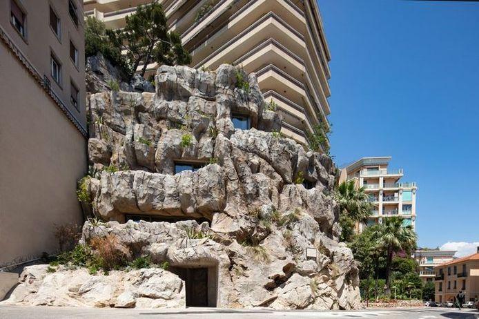 Op de achtergrond de karakteristieke appartementen van Monaco, inclusief blauwe lucht. De rotspartij op de voorgrond blijkt een luxueuze woning.