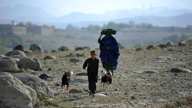 Een Afghaans jongetje vlucht met zijn moeder weg van een dorp, omdat het Afghaanse leger er actie onderneemt tegen Taliban-strijders. Beeld epa