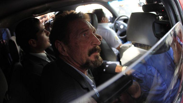 John McAfee wordt door agenten van de immigratiedienst naar het vliegveld van Guatemale begeleid. Beeld reuters