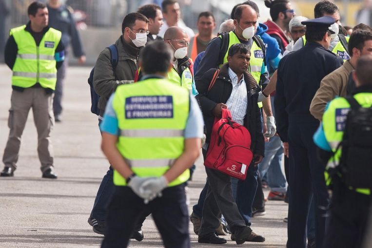 Agenten houden toezicht wanneer migranten aan boord van een ferry gaan in de haven van  Mytilini.