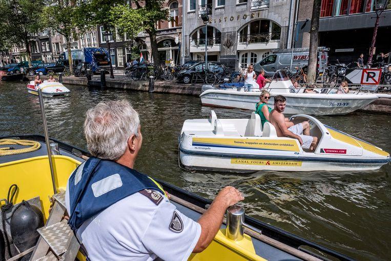 Ale waarschuwt de schipper van de motorboot dat hij ligt afgemeerd waar dat niet is toegestaan. Beeld Patrick Post