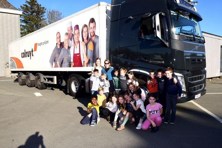 Juf Britt en de kinderen van het derde leerjaar bij haar truck.