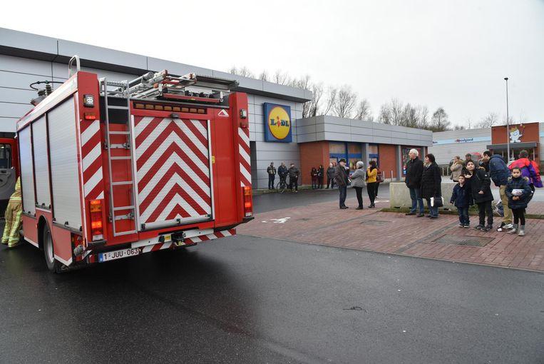 De geëvacueerde klanten wachten buiten op de parking.