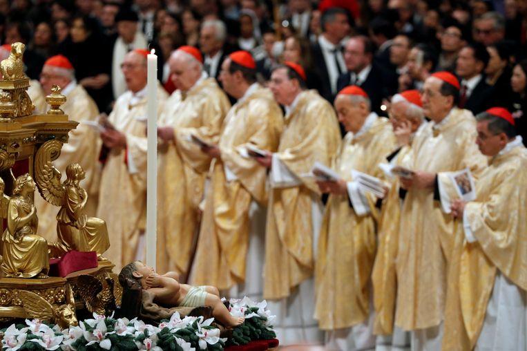 Kardinalen in gouden gewaden wonen de kerstnachtmis van de Paus bij in Rome.