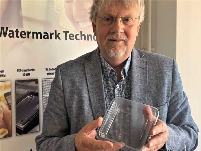 Johan Kerver, ceo van FiliGrade in Twello en uitvinder van de 'onzichtbare code' voor plastic voedselverpakkingen. Zoals het bakje dat hij vasthoudt. Als je heel goed kijkt zie je kleine  puntjes die in een curve naast elkaar staan.