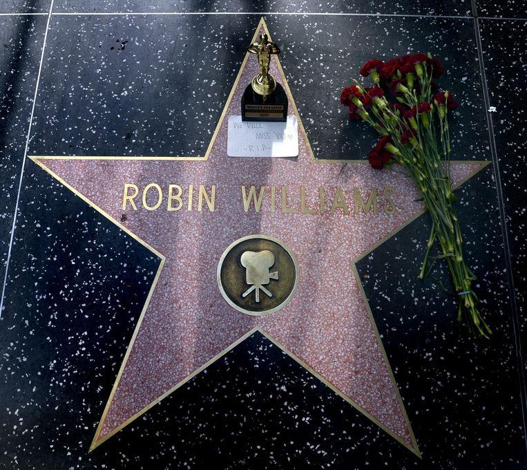 Bloemen en een Oscarsouvenir zijn gelegd op de Walk of Fame-ster van Williams in Hollywood na het overlijden van de populaire Amerikaanse acteur. Beeld epa