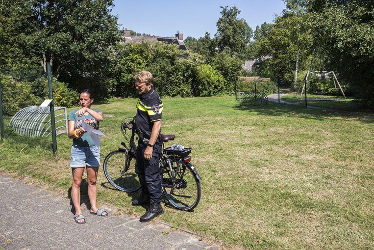 Een wijkagent met e-bike in Assen praat met een buurtbewoner. Beeld ANP