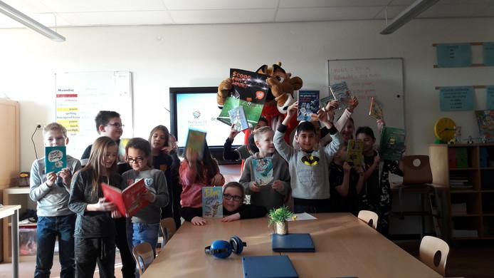 Groep 5 van basisschool De Triangel en Willem II-mascotte Kingo geven de aftrap voor het leesproject Scoor een Boek!.